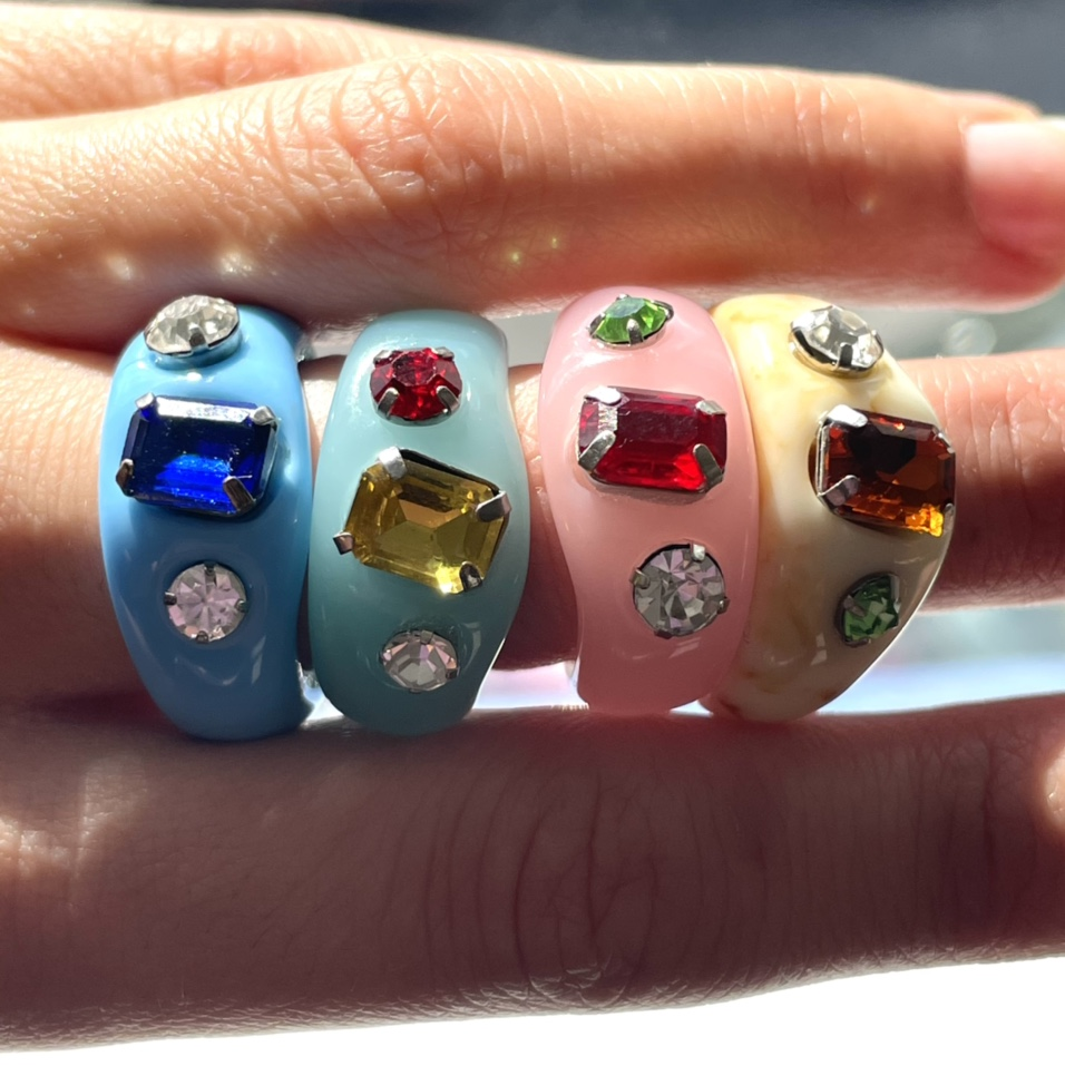 Finger wearing four resin rings in blue, pink and yellow with multi-coloured gems