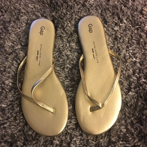 83eb7cb65384 The are a pair of gold Gap flip flops! - Depop