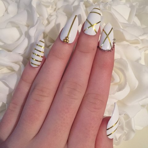 White Stiletto Nails With Gold Tape Designs And Studs