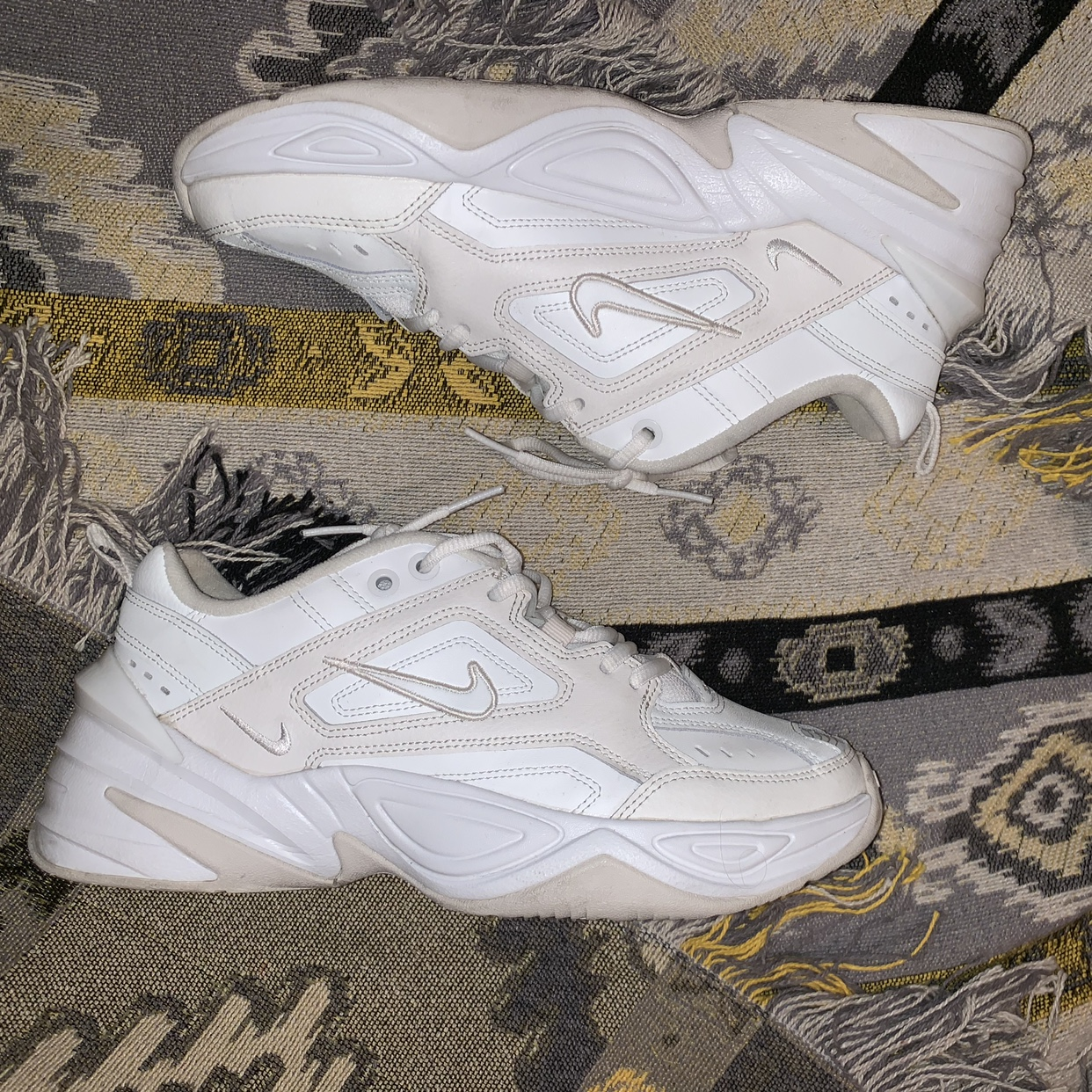 White and nude Nike Tekno sneakers. The