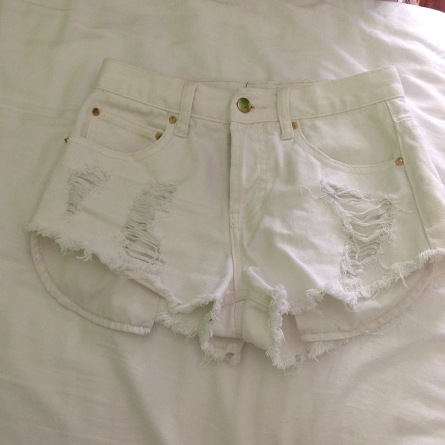 White high waisted shorts. Distressed. Has pockets that stick out ...