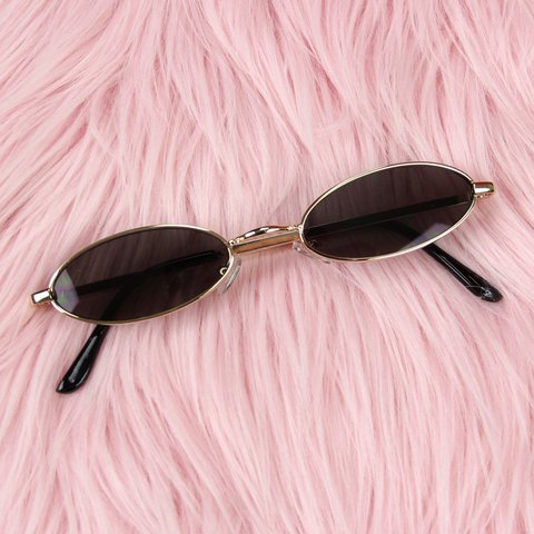 be233e60064 Slim Oval Sunglasses featuring gold metal frames and black - Depop