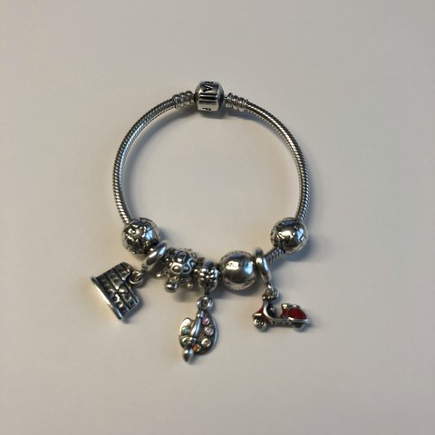 ae639a712 An authentic Pandora bracelet with 2 clips and 5 charms. In - Depop
