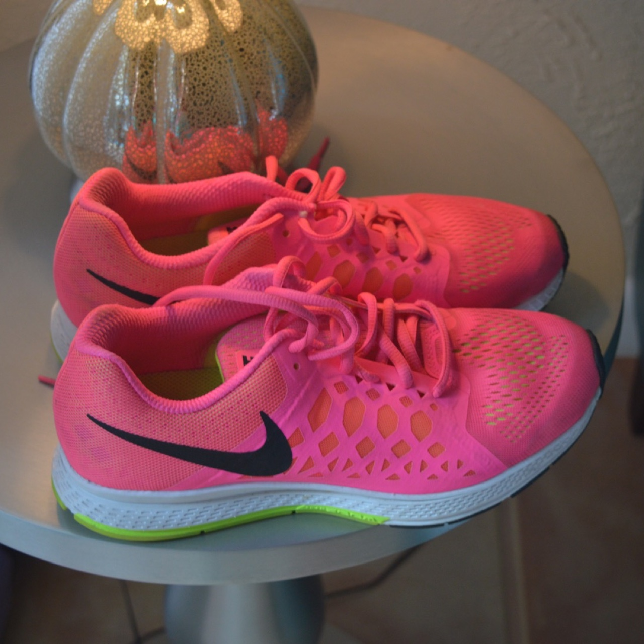 Neon pink Nike running shoes with some