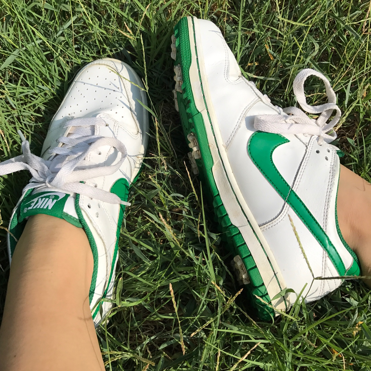 White Nike sneakers with green swoosh