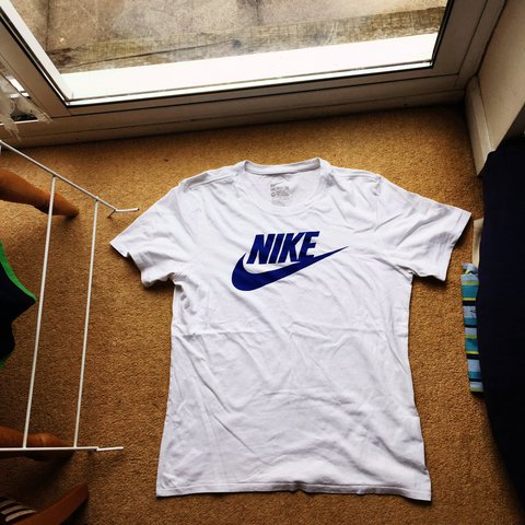 ea22e706 @arobson8. 2 years ago. Leicester Forest East, United Kingdom. Nike Plain  white tee with blue Nike logo. Short sleeve. Athletic top